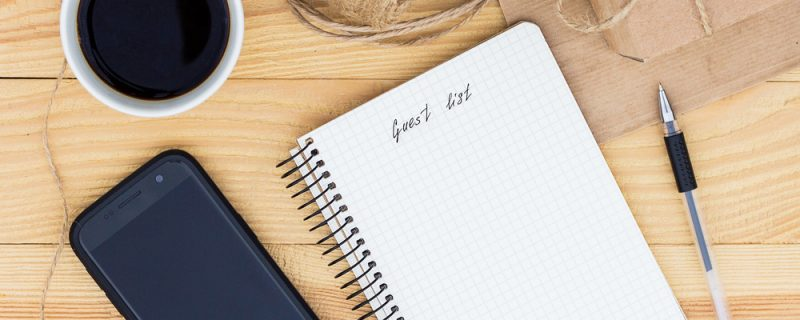 A notebook with an inscription Guest list laying on wooden table. It is surrounded by phone, black pen, cup of coffee, present, rope twine and a paper bag.