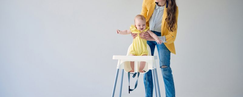 Beautiful stylish mother putting baby girl in high chair
