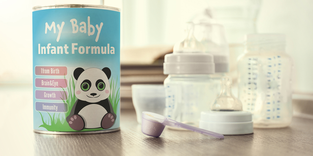 Can and scoop with powdered baby milk formula on wooden table