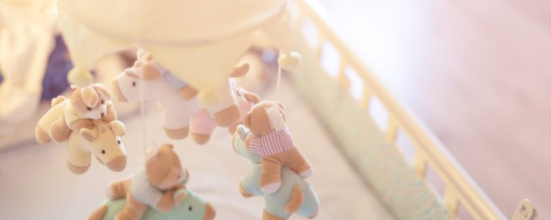 Close-up baby crib with musical animal mobile