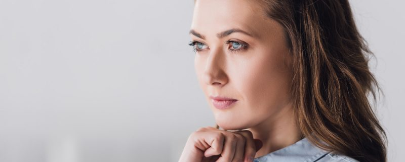 Close-up portrait of thoughtful adult woman looking away