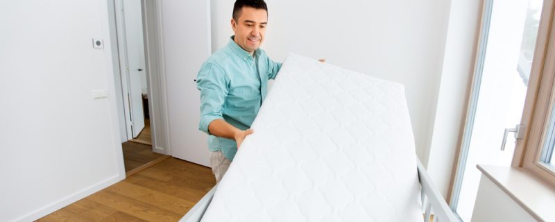 Father arranging baby bed with mattress at home