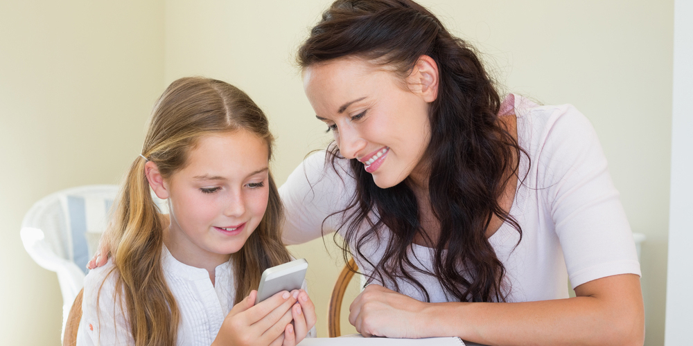 Girl with mother using cell phone at table