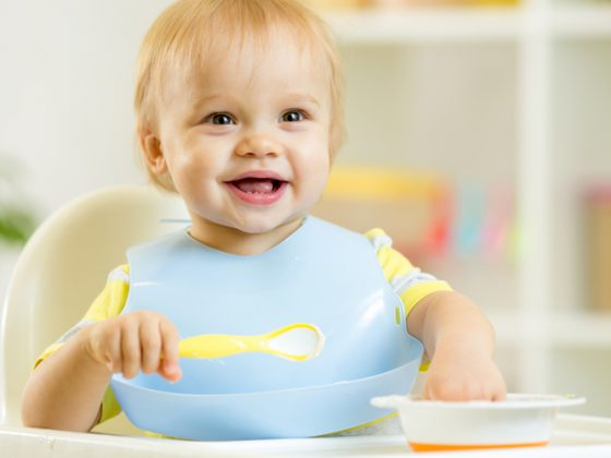happy cute baby kid boy eating dood itself with spoon