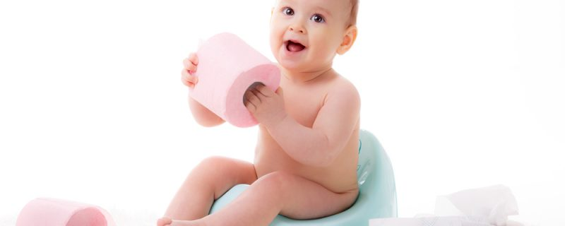 Little girl sitting on potty with toilet paper