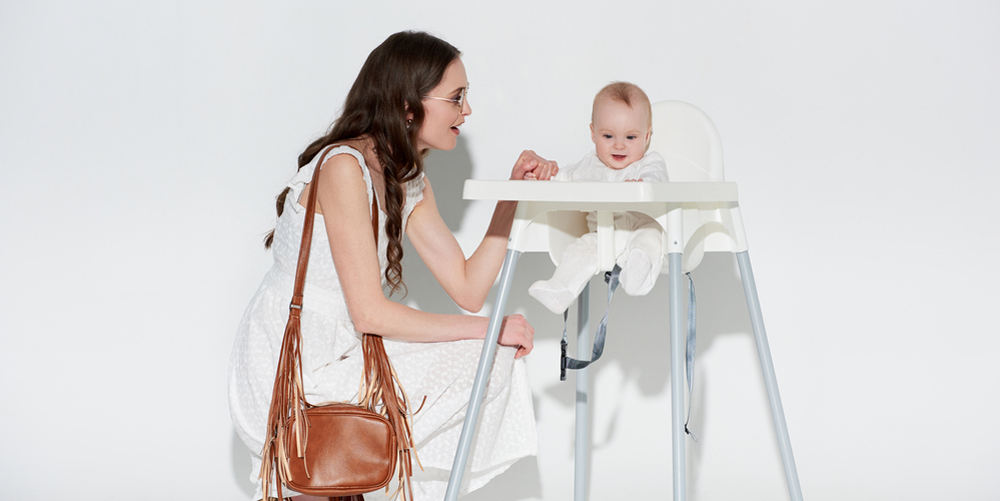 Stylish smiling woman looking at adorable infant daughter sitting