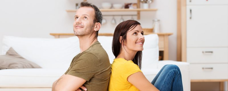 Young couple relaxing on the floor at home sitting barefoot back to back each looking up into the air with a thoughtful smile as they plan their future together